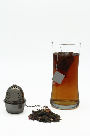 infuser: dry leaves, glass of Tea and its infuser Stock Photo