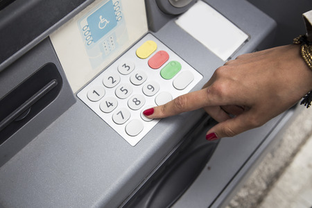 withdrawing: woman with polished nails withdrawing money at atm