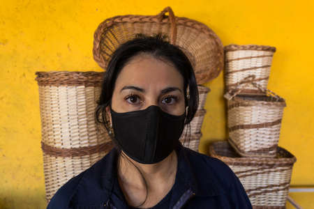 Portrait of Latin artisan woman with mask, with at work work clothes 版權商用圖片