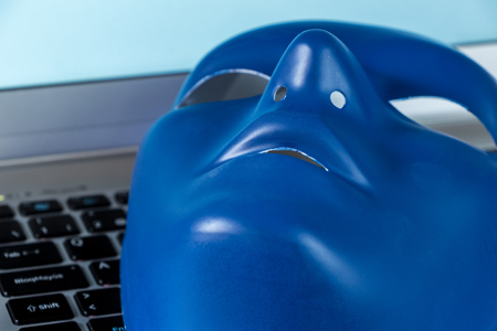Identity on Social Networks concept. Blue mask on computer keyboard on blue screen Stock Photo