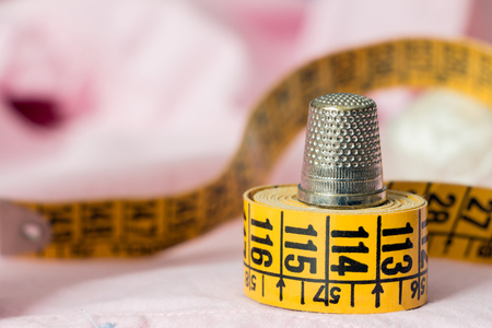 Thimble on yellow tape measure on pink background. Sewing hobby concept Stock Photo