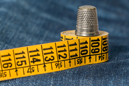 Thimble on yellow tape measure on blue denim background. Sewing hobby concept Stock Photo