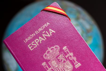 Pasaporte español, bandera española y globo terráqueo. Viajar por el concepto del mundo