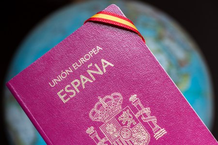 Spanish passport, Spanish flag and earth globe. Travel around the world concept