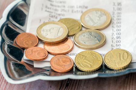 Trinkgeld in Europa. Rechnung und Zahlung, Münzen auf Trinkgeldschale
