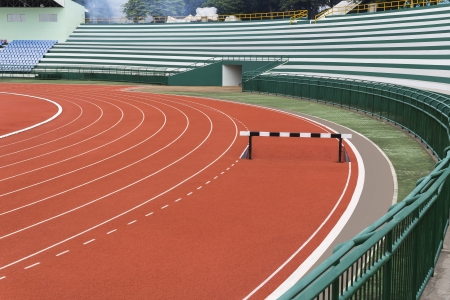 Hurdle on red running track in stadium