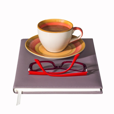 Coffee cup on notebook with red glasses isolated on white background