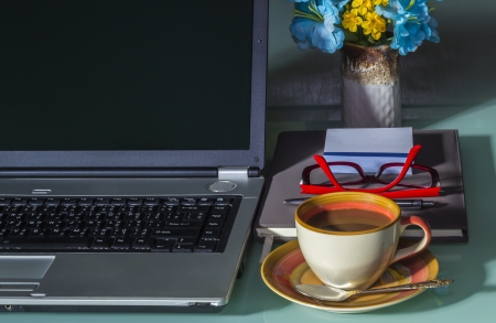 Laptop with coffee cup  on office table photo
