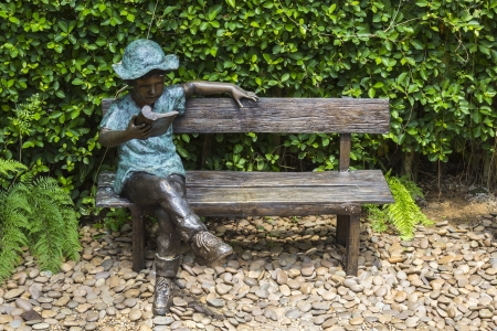 Statue reading a book sitting on bench in garden Stock Photo