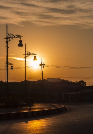 Silhouette of street lamp with sunrise background photo