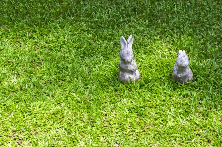 Closeup two rabbit statue on green grass photo