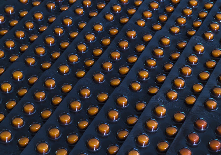 Closeup row of orange pills in black blister pack Stock Photo