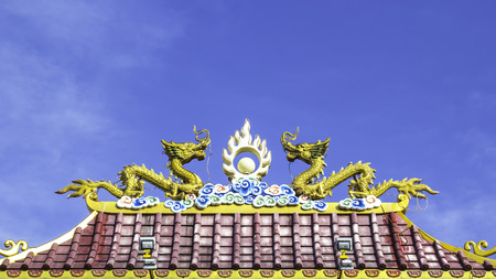 Twin dragon statue on chinnese roof with blue sky background