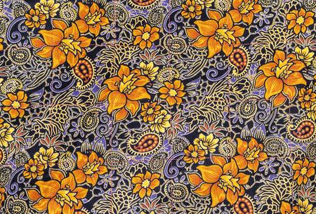 Beautiful orange flowers on batik fabric background