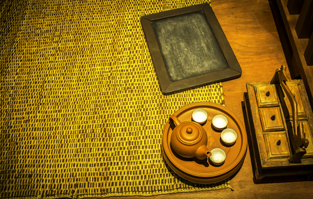 Wooden black board and teapot with cup on the bamboo mat