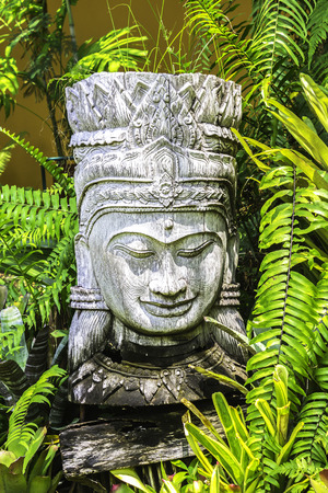 Wooden carving decorated with green plant in the garden