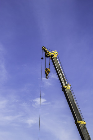 Industrial crane and hook white blue sky background
