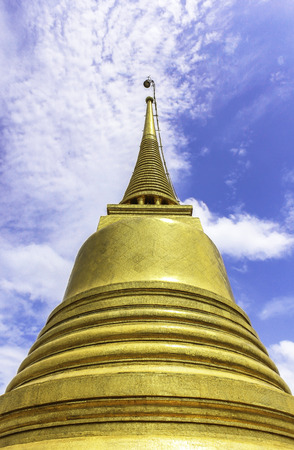 Golden pagoda in temple thailand with blue sky background