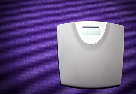 Digital weight scale on purple carpet background Stock Photo