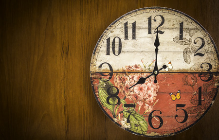 Old vintage clock on brown wooden background