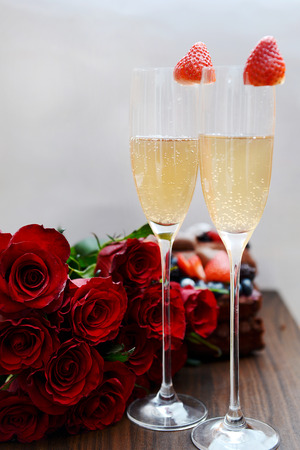 Filled with Champagne Flutes , Bunch of Dark Red Roses and Chocolate Cake on background photo