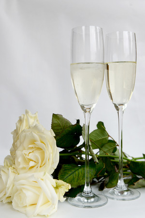 Champagne Flutes Filled with Champagne and Bunch of White Roses on the background photo