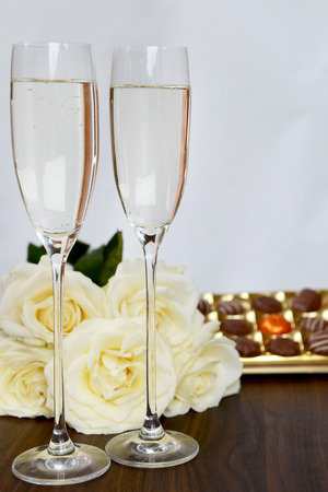 champagne flutes: Champagne Flutes Filled with Champagne, Box of Chocolate and Bunch of White Roses on the background Stock Photo