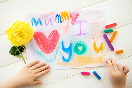 Little Girl is Drawing Postcard with Pastels Chalks for Mothers Day. She wrote \Mummy I Love You\. Yellow Rose is laying nearby. photo