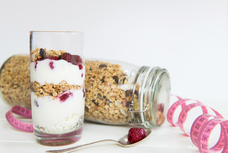 healthy snack: Homemade granola in glass jar with Tape Measure nearby. Healthy snack  granola with yogurt and berries in a glass