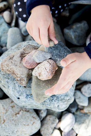 quin: Girl playing with Sea Rocks in Landudno, England, UK