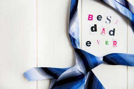 Best Dad Ever Letters Cut out from Magazine with Blue Tie laying on White Wooden Background