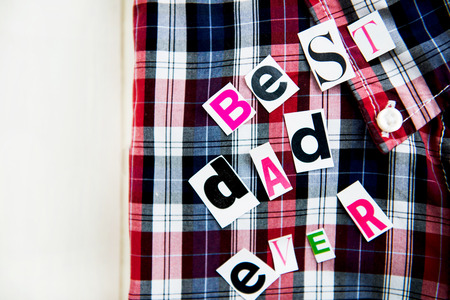 Best Dad Ever Letters Cut out from Magazine with Checked Shirt laying on White Wooden Background