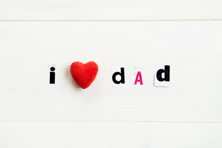 I Love Dad Letters Cut out from Magazine with Red Heart laying on White Wooden Background Imagens
