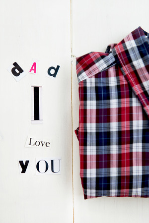 Dad I Love You Letters Cut out from Magazine with Checked Shirt laying on White Wooden Background