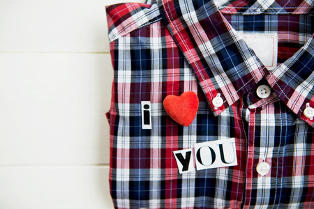 I Love You Letters Cut out from Magazine with Checked Shirt laying on White Wooden Background