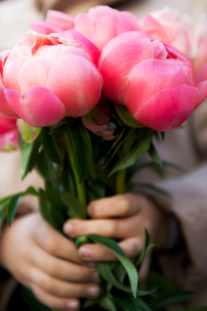 Little Girl Holding Bunch of Bright Pink Peonies