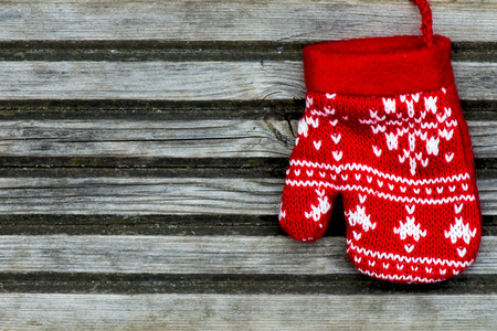 Christmas Red Knitted Mitten with Snowflake Motives on wooden background