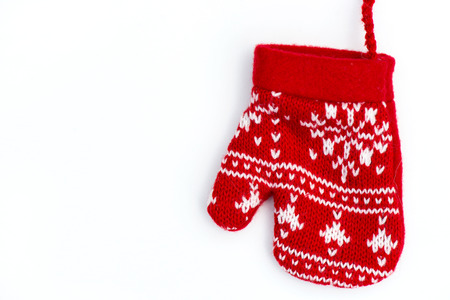 Christmas Red Knitted Mitten with Snowflake Motives on white background