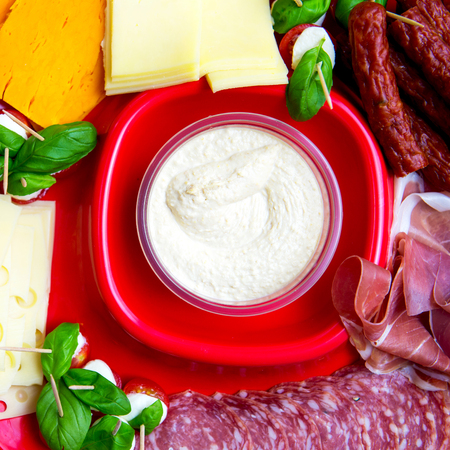 salami slices: Snacks on the Red Plate, Hummus, Red Leicester Cheese, Emmental Cheese, Basil, Tomato, Mozarella, Kabanos, Prosciutto, Salami Slices Stock Photo