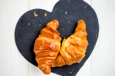 blacked: Two Fresh Croissants are ready for the Breakfast and laying on the Heart Shaped Blacked Coaster, Top View