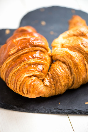 blacked: Two Fresh Croissants are ready for the Breakfast and laying on the Heart Shaped Blacked Coaster, Shallow DOF, Selective Focus Stock Photo