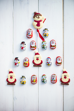 sweettooth: Chocolate Santas, Snowman and Biscuits laying in a form of Christmas Tree on White Background Stock Photo