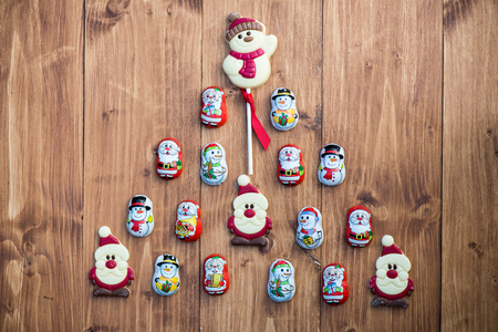 sweettooth: Chocolate Santas, Snowman and Biscuits laying in a form of Christmas Tree on Wooden Background