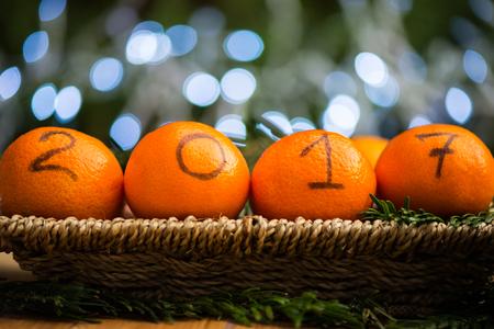 Nieuwjaar 2017 is Coming Concept. Nummers geschreven in zwarte inkt op de sinaasappelen die in de mand met Pine Sticks en Xmas Lights op de achtergrond liggen