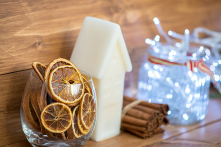 warm things: Sweet Home Concept with Different Cute Xmas Things on the Wooden Shelf, such as White Candle House, Xmas Lights in the Glass Jar, Cinnamon Sticks and Citrus Dried Slices Stock Photo