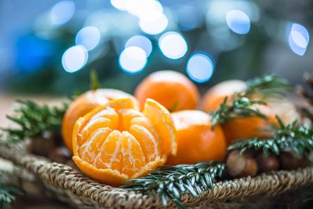 Verse Clementines of Mandarijnen in de mand op bruine houten tafel met de Lichten van Kerstmis en boomtakken