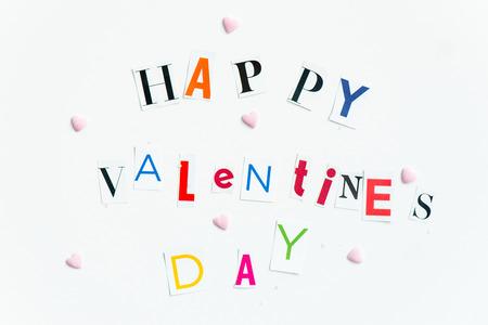 Coloridos Happy Valentines Day letras recortadas de las revistas con pequeños caramelos en forma de corazón en las inmediaciones de madera en el fondo blanco