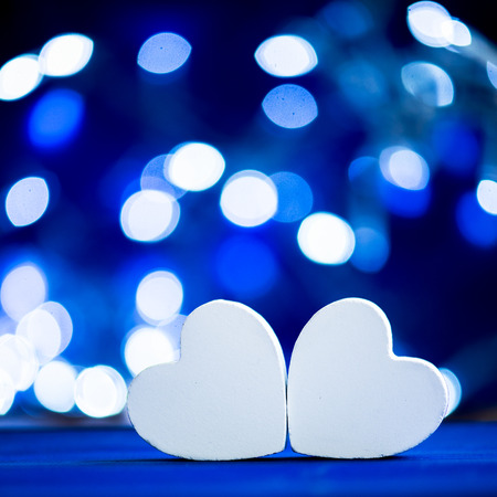 anniversary backgrounds: Close up of two white hearts on wooden table over blue bokeh background