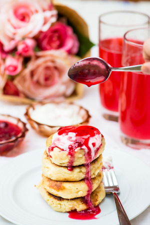 recipe decorated: Fried Homemade Cottage Cheese Pancakes or Russian Ukrainian Syrniki with Sweet Berry Sauce and Sour Cream