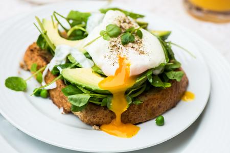 desayuno: Desayuno saludable con pan integral pan tostado y huevo escalfado con ensalada de lechuga, aguacate y guisantes. Jugo de naranja y rodajas de naranja en el fondo. Foto de archivo